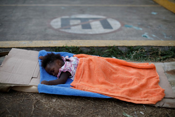 A migrant child sleeps outside of Siglo XXI migration facility in Tapachula