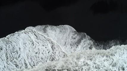 Wall Mural - Aerial footage of waves breaking against black sand beach in Iceland.