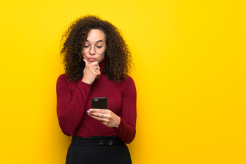 Dominican woman with turtleneck sweater with a mobile and thinking
