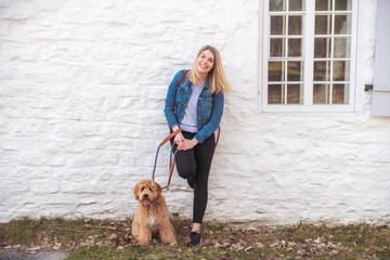 Labradoodle Dog and woman outside close to a white wall brick
