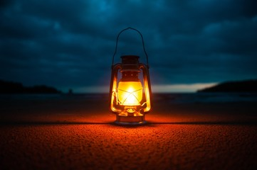 Vintage portable oil lantern on the ground on a cloudy twilight.