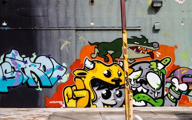 Colourful grafitti of a child and dogs on a building concrete wall