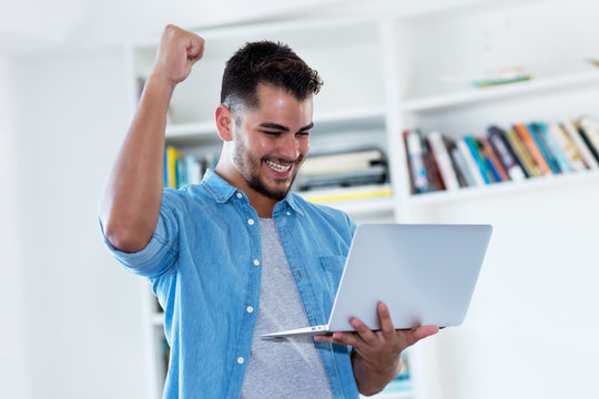 Cheering mexican hipster man with beard and computer