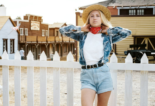 Young attractive girl with long blonde hair wearing a white empty t-shirtand jeans shorts is staying on a western town background. Horizntal mock-up style.