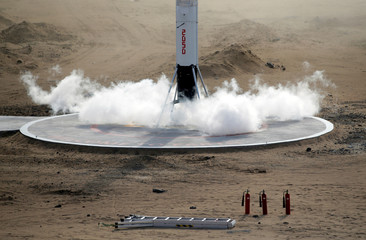 Fire extinguishers are placed next to the landing site while the LinkSpace's reusable rocket RLV-T5 lands during a test launch in Longkou