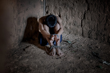 little boy tied with chained. Abused and tortured concept. Human trafficking concept.