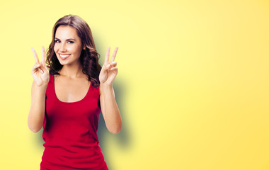 Woman showing two fingers or victory gesture, on yellow