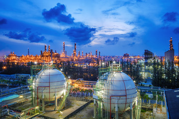 Gas storage sphere tanks and pipeline in oil and gas refinery industrial plant with glitter lighting industry estate at twilight