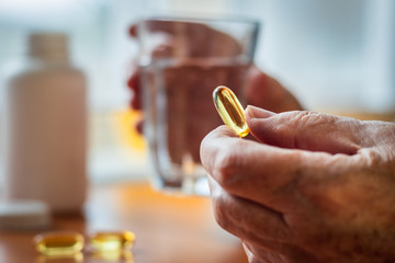 Senior woman holding omega-3 fish oil nutritional supplement and glass of water