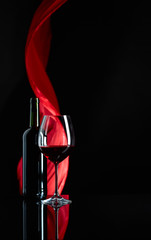 Spoed Foto op Canvas Wijn Wineglass and bottle of red wine on a black reflective background.