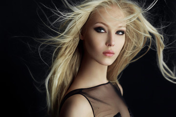 Graceful blonde girl in perfect make up with hair scattered by the wind, isolated on a black background.