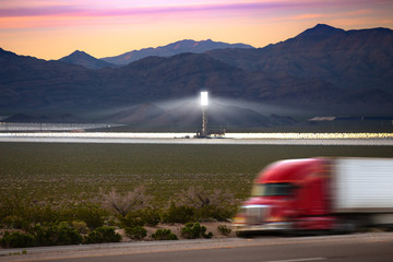 Renewable energy concept, beautiful solar thermal power plant in nature versus fossil fuel based trucking industry