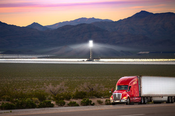 An eighteen wheeler with the future of renewable clean steam and solar energy in background