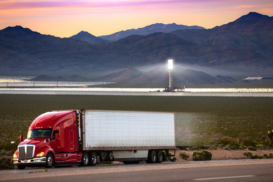 An oil and diesel powered truck with solar power plant in the background, clean thermal energy versus fossil fuels