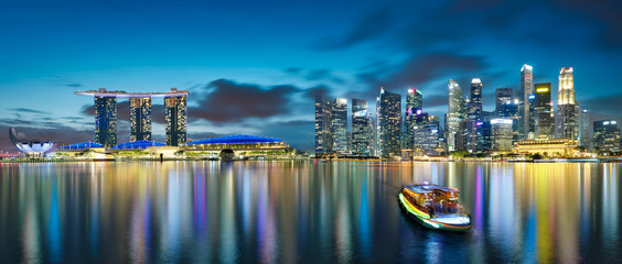Fotomurales - Panorama view of Singapore city skyline with tourist boat at night . Travel asia concept .