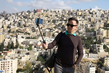 A tourists poses for selfie pictures during his visit to the Amman Citadel, an ancient Roman landmark, in Amman