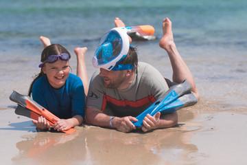 Fototapeta Szczęsliwa dziewczynka spędza czas na plaży z tatą i nurkuje w morzu obraz