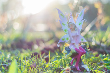A beautiful background for a fantasy deisgn. A blurred figure of a fairy girl on a green field.