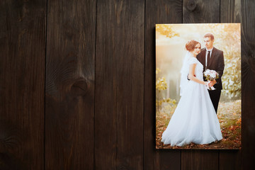 Photo canvas print. Wall decor. Sample of stretched wedding photography with gallery wrap. Bridal portrait hanging on brown wooden background. Front view with copy space