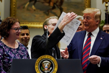 Davis shows U.S. President Trump a surprise medical bill while Trump spoke to reporters at the White House in Washington