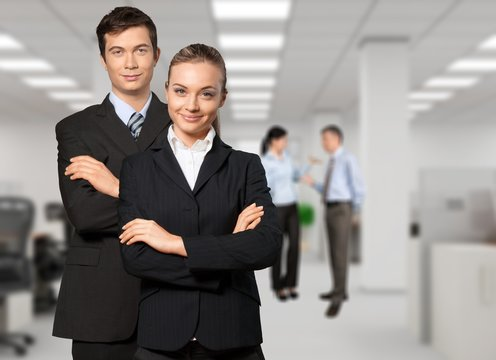 Confident young Business couple with crossed hands on background