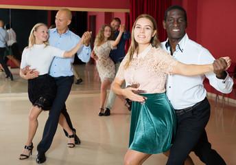 4f631ed98f4dd Positive adult pairs enjoying dancing salsa in modern dance studio