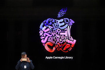 A visitor takes a picture on their phone during the grand opening and media preview of the new Apple Carnegie Library store in Washington