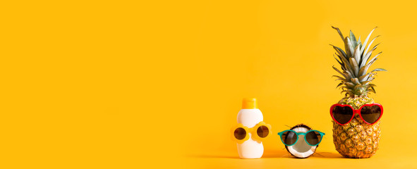Pineapple and coconut wearing sunglasses with sunblock on a solid background Wall mural