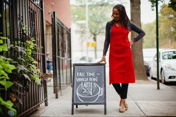 Smiling female owner with blackboard standing on sidewalk in city