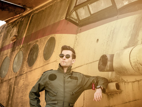 A handsome young pilot standing next to an old plane