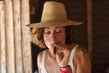 Western girl smoking a cuban cigar with a straw hat. ViÒales, Cuba