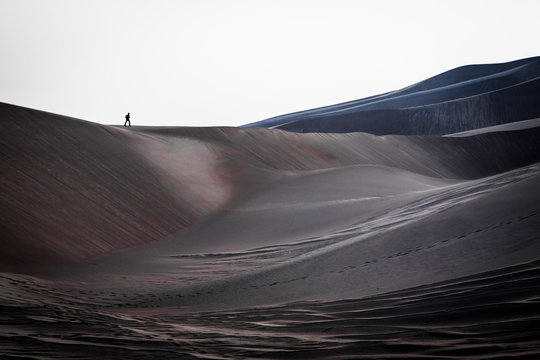 Hiker crosses a dune at Great Sand Dunes National Park, CO