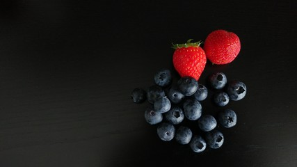 Blueberries and Strawberries on Black Background