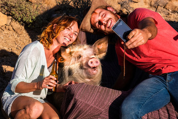 Happy alternative nature animal lover couple of cheerful people enjoy and have fun taking selfie picture with a funny pig in friendship - different lifestyle for millennials outdoor