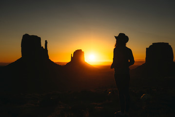USA, Utah, Monument Valley, silhouette of woman with cowboy hat watching sunrise