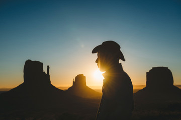 USA, Utah, Monument Valley, silhouette of man with cowboy hat at sunrise
