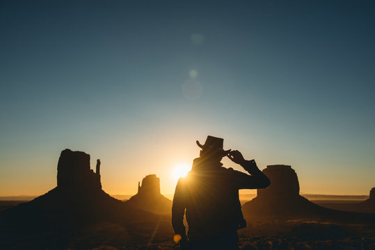 USA, Utah, Monument Valley, silhouette of man with cowboy hat watching sunrise