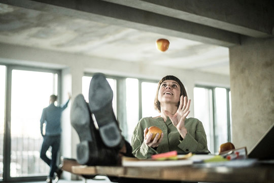 Woman juggling apples in the office, sitting with feet on desk