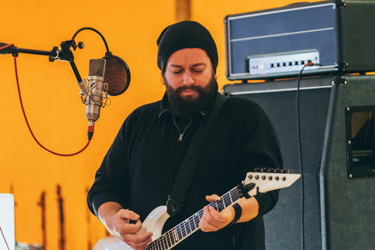 Adult man in music studio playing a guitar and singing in a microphone