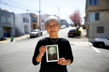 Paulette Liang, 76, poses for a portrait with a photo of her great-grandfather, Lum Ah Chew, a Chinese Transcontinental Railroad worker, near her home in San Francisco