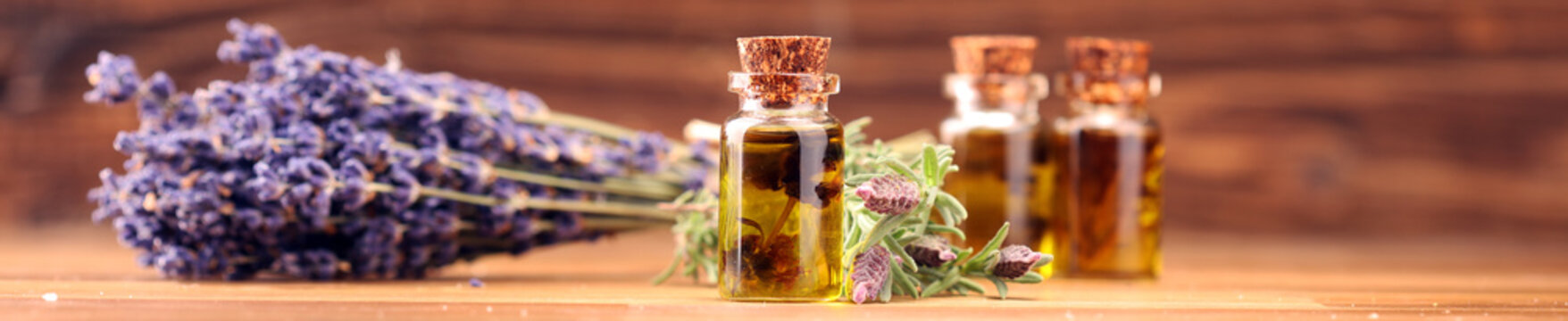 essential lavender oil in a glass bottle on a background of fresh flowers