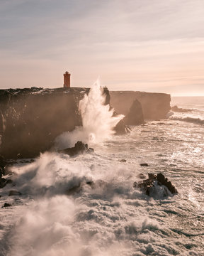 Storm waves at the west coast of Iceland and Svˆrtuloft Lighthouse at the distance