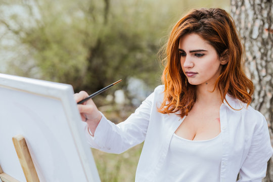 Young woman painting in countryside