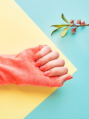 From above of crop female hand in sweater and with manicure of peach color on yellow and blue paper background
