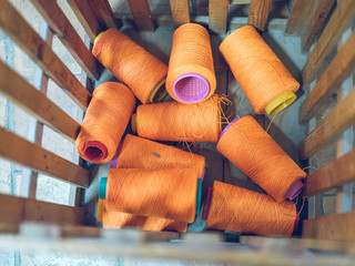 Bunch of spools with orange thread placed inside wooden container on factory