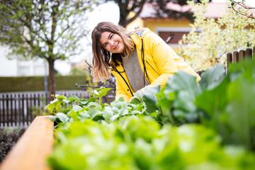 Junge Frau bei der Gartenarbeit an einem Hochbeet