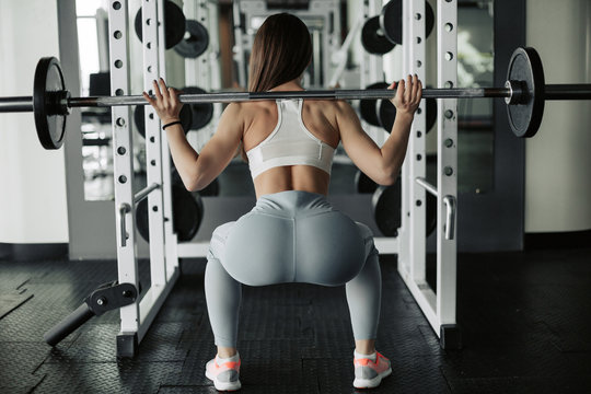 Attractive young sports woman with barbell. Doing squats. Back view.