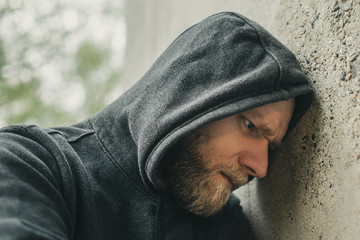 angry man leaning his head against a wall