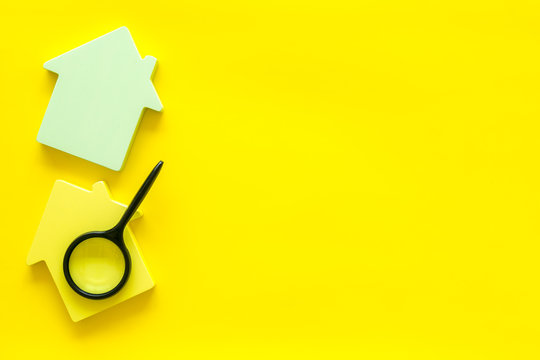 Search for a new house concept with house figure and magnifier on yellow office desk background top view space for text