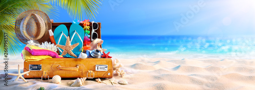 Fototapete Full Suitcase With Accessories On Tropical Beach